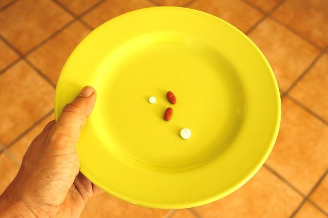 ruka, talíř, čtyři prášky