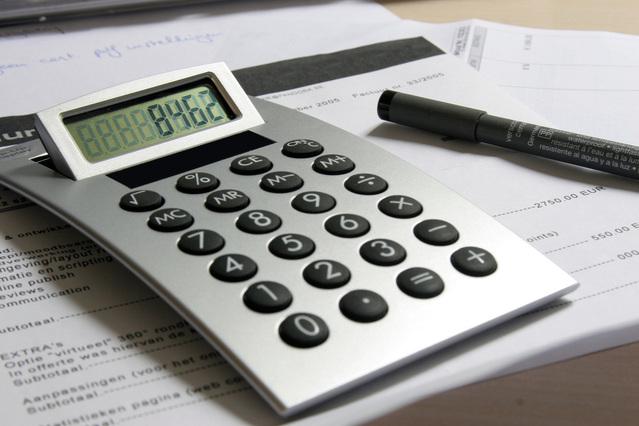kalkulačka s vypočítanou částkou na stole